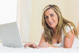 Content woman looking at camera using a laptop lying on a bed