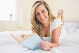Joyful woman looking at camera reading a book lying on her bed