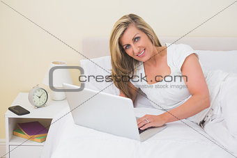 Pleased woman using a laptop lying on her bed