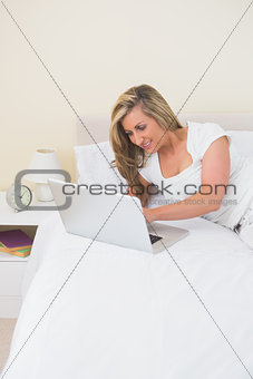 Joyful woman lying on her bed using a laptop