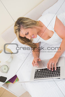 Cheerful woman typing on a laptop and lying on her bed
