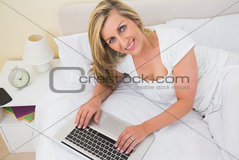 Happy woman using a laptop lying on her bed