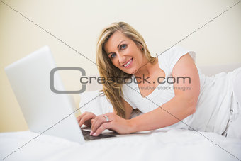 Cheerful woman typing on a laptop lying on her bed