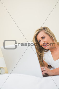 Happy woman typing on a laptop lying on her bed