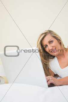Amused woman typing on a laptop lying on her bed