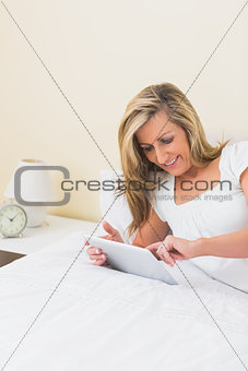 Content woman using a tablet pc lying on her bed