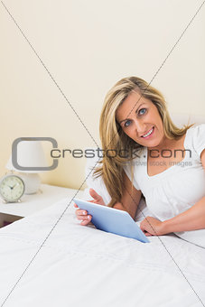 Amused woman using a tablet pc lying on her bed
