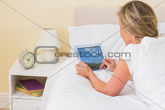 Concentrated woman using a tablet pc lying on her bed