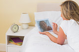 Thoughtful woman using a tablet pc lying on her bed