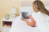 Focused woman using a tablet pc lying on her bed