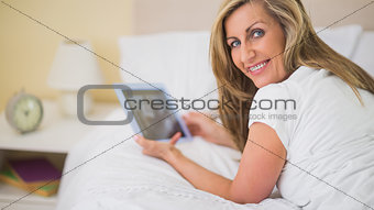Happy woman using a tablet pc lying on her bed