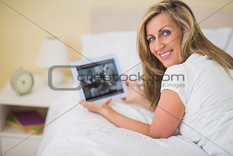 Pleased woman using a tablet pc lying on her bed