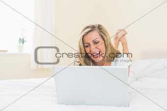 Laughing woman using a laptop lying on her bed