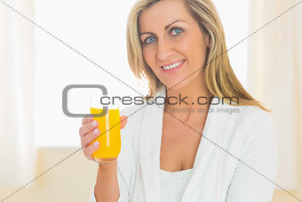 Content woman looking at camera enjoying a glass of orange juice