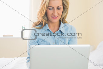 Thoughtful woman sitting on a bed using her laptop
