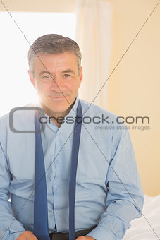 Happy man looking at camera sitting on a bed