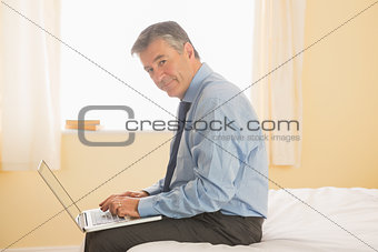 Thoughtful man using a laptop sitting on a bed