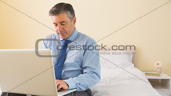 Thoughtfulman using a laptop sitting on a bed