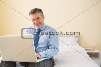 Smiling man using a laptop sitting on a bed