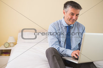 Content man using a laptop sitting on a bed