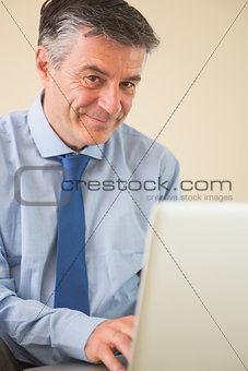 Pleased man using a laptop sitting on a bed