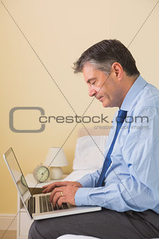Concentrated man using a laptop sitting on a bed
