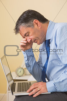 Tired man using a laptop sitting on a bed