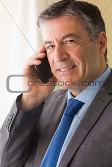 Smiling man calling someone with his mobile phone