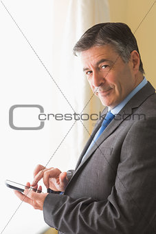 Amused man texting on his mobile phone