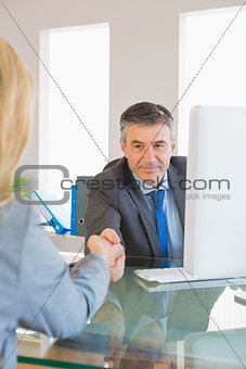 Amused businessman shaking the hand of a interviewee