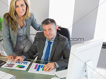 Businesspeople posing at camera studying figures