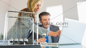 Businesswoman explaining something on the computer to a concentrated businessman