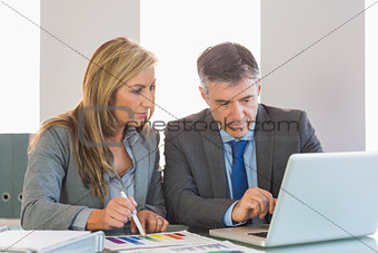 Attentive businessman showing something on computer to an attentive businesswoman