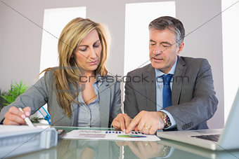 Two unsmiling business people pointing at a graphic