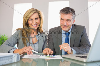 Two pleased business people smiling at camera analysing a graphic