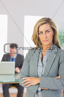 Serious businesswoman looking at camera crossed arms with a businessman working on background