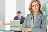 Unsmiling businesswoman looking at camera crossed arms with a businessman working on background