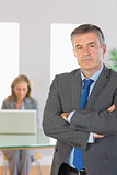 Irritated businessman looking at camera crossed arms with a businesswoman working on background