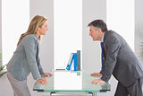 Two angry businesspeople arguing on each side of a desk
