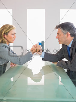 Two annoyed businesspeople having an arm wrestling sitting around a table