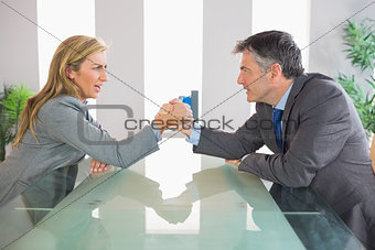 Two upset businesspeople having an arm wrestling sitting around a table