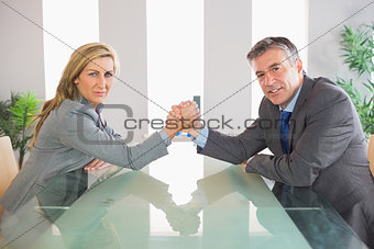 Two serious businesspeople having an arm wrestling sitting around a table
