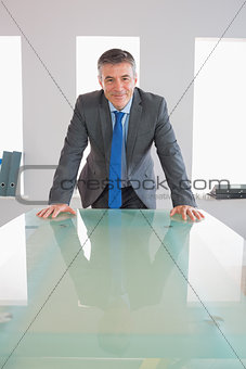 Laughing businessman standing in front of a desk