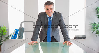 Happy businessman standing in front of a desk