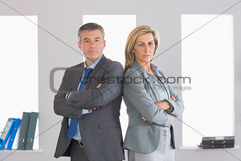 Two unsmiling businesspeople looking at camera standing back to back with crossed arms
