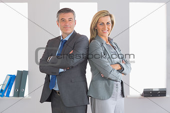 Two smiling businesspeople looking at camera standing back to back
