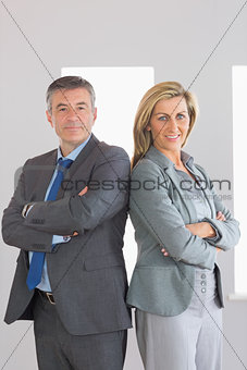 Two content businesspeople looking at camera standing back to back