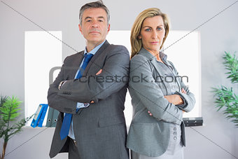 Two serious businesspeople looking at camera standing back to back