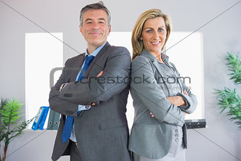 Two happy businesspeople looking at camera standing back to back