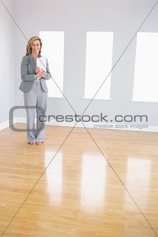 Happy realtor standing in a room holding documents